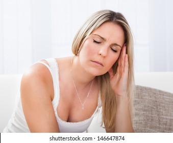Woman with a migraine sitting holding her throbbing head