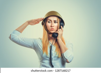 Woman in military armor cap helmet equipment of World War II period talking at phone giving her salute to the captain. Person in white formal shirt, long blonde hair isolated on light green background