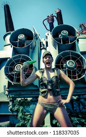 Woman in military camouflage shoots himself from a water pistol on the industrial background. Too hot to live concept.