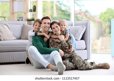 Woman in military uniform with her family at home