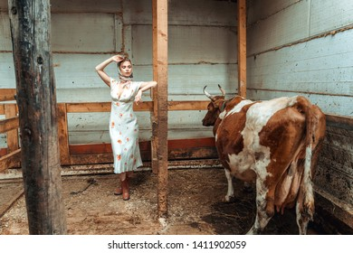 the woman is a milkmaid in the cowshed , farm.