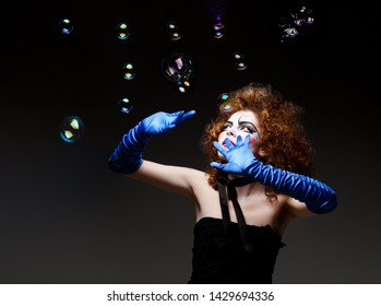Woman mime with theatrical makeup and soap bubbles.