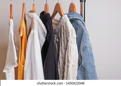Woman minimalist wardrobe in white and denim on hangers close-up