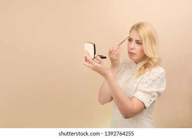 a woman with a mirror in her hand makeup corrects eyebrows with a make-up brush. A blonde girl with blue eyes in a white vintage dress on a beige yellow cream background put her makeup on.