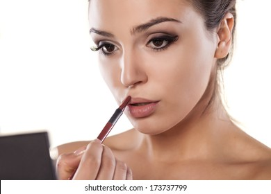 woman with a mirror that is applied a lip liner