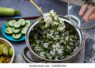 Woman mix hot cooked, steamed Indian basmati rice or Chinese rice with laminaria seaweed with spoon in steel pan.