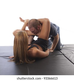 Woman in MMA attire applying an ankle choke against an opponent on black mat