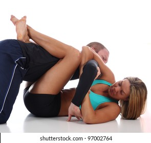 Woman in MMA attire applying a Jiu-Jitsu kimura armlock