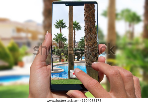 Woman with mobile phone photos exotic resort with pool.