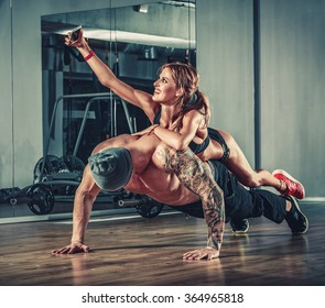 woman with mobile phone training with muscular handsome man bodybuilder in gym