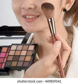 Woman model with cheek brush and professional makeup hand