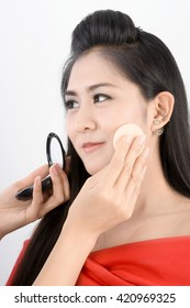 Woman model with cheek puff powder and professional makeup hand