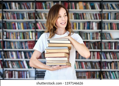 Woman model college student working at library holds bunch of books in hands, looking smart. bookshelves at the library.