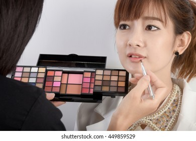 Woman model and cosmetic professional makeup use lipstick brush