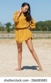 Woman model on a beach in a dress