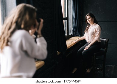 Woman model posing while sitting on chair in photo studio for unrecognizable female photographer which shooting with camera. Concept of creative work in photo studio, backstage job.