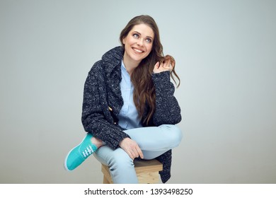 Woman model sitting on  wooden stool against white wall. Isolated studio portrait.