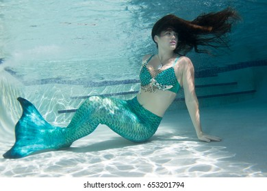 Woman model underwater wearing a green mermaid tail, with matching green stylized shell top.