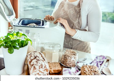 Woman in a modern kitchen among the ingredients for homemade bread prepares a machine for baking. Photo taken in the light of natural sun and studio lamps. It contains artistic noise