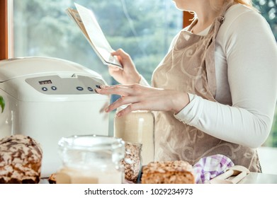 Woman in modern kitchen reads the instructions for a machine that bakes bread. Photo taken in the light of natural sun and studio lamps. It contains delicate artistic noise and a vintage color grading