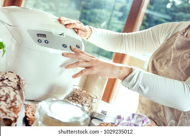 Woman in a modern kitchen sets a machine for baking homemade bread. Photo taken in the light of natural sun and studio lamps. It contains delicate artistic noise and a vintage color grading
