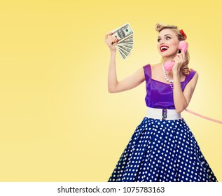Woman with money, talking on phone, dressed in pinup style dress in polka dot, with copyspace area for slogan or advertising text message, on yellow background. Retro and vintage concept studio shot.