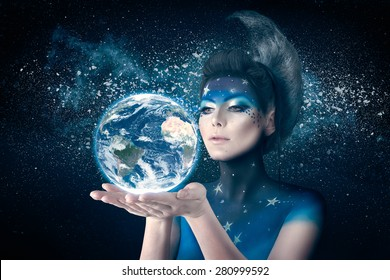 Woman with moon inspired bodyart and hairstyle holding planet earth in hand with care. Element of this image furnished by NASA