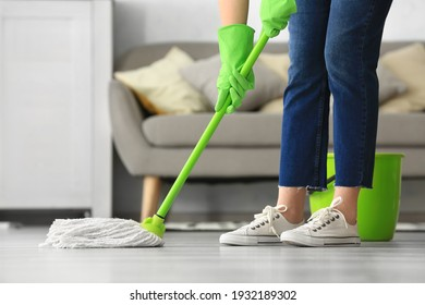 Woman mopping floor in room