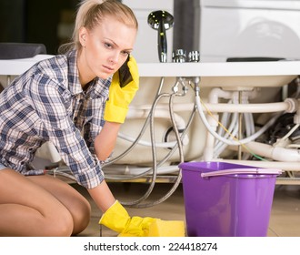 Woman mopping up. She is calling to plumbing.