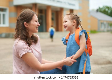 the woman morally supports the daughter holding hands encourages the child. mother accompanies students to school. friendly family goes to kindergarten.happy little girl with a caring mom