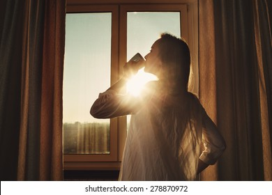 Woman in the morning. Attractive sexy woman with neat body is drinking hot tea or coffee from her cup and looking at the sunrise standing near the window in her home and having a perfect cozy morning.