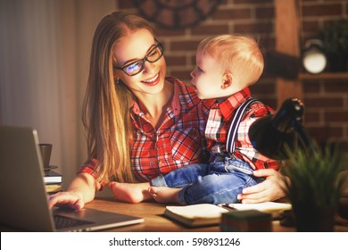 woman mother working  with a baby at home behind a computer via the Internet