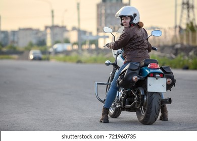 Woman a motorcyclist looking back when standing on motorbike on asphalt road, copy space
