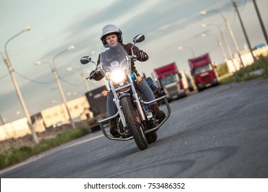 Woman motorcyclist riding solo on chopper with turning on headlight on asphalt urban road