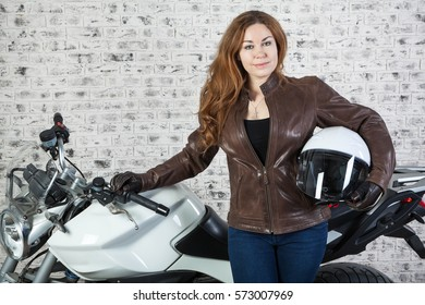 Woman a motorcyclist standing with helmet in hand near her bike in garage, brick wall background