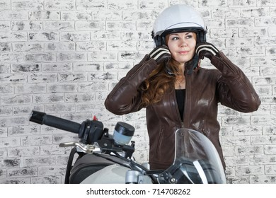 Woman a motorcyclist wearing white helmet while preparing to drive out the garage