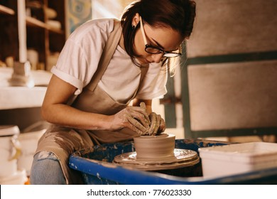 Woman moulding clay on pottery wheel. Craftswoman making pot in workshop.