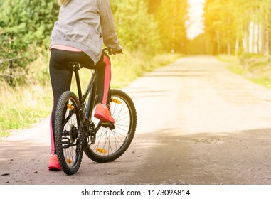 Woman with a mountain bicycle along country road. Healthy lifestyle and sport concept