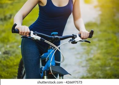 Woman mountain biking and holding handlebars