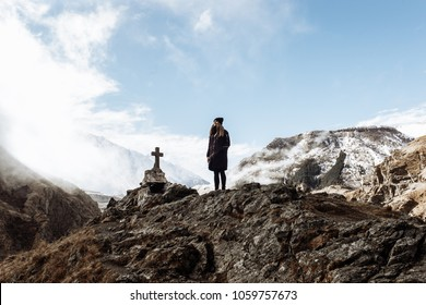 Woman in the mountain. Cross sign in the mountain