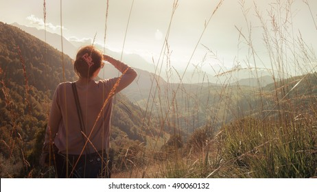 woman in the mountain is looking far away, traveling during autumn season