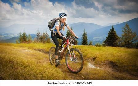 Woman mountain-bike riding on ridge with Carpathian Mountains
