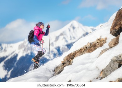 Woman mountaineer during a descent with crampons on snowy slope