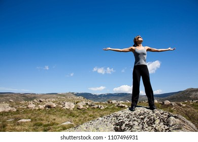 woman in the mountains doing breathing exercises