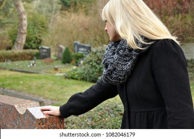 A woman in mourning over the loss in front of a tombstone at the grave of a deceased relative in a cemetery
