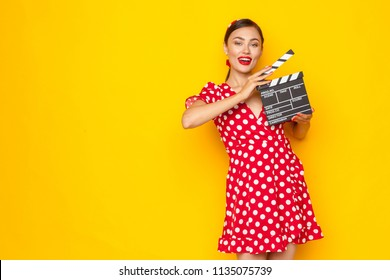 Woman with movie clapper board. Young retro pin-up girl