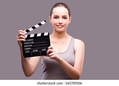 Woman with movie clapper on gray background