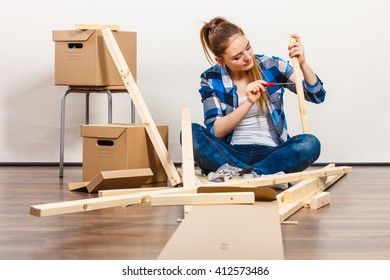Woman moving into new apartment house assembling furniture using scredriver. Young girl arranging interior and unpacking boxes. DIY.