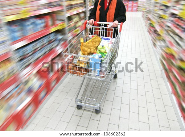 woman is moving shopping cart, the supermarket is motion-blurred
