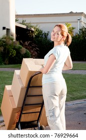 A woman moving with a stack of cardboard boxes on a trolly